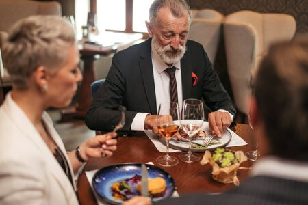Hungry restaurant visitors eat delisious food, look at meal with appetite. Close up of elderly man looking at plate silently, holding silver fork and knife ready to cut meat for small pieces.