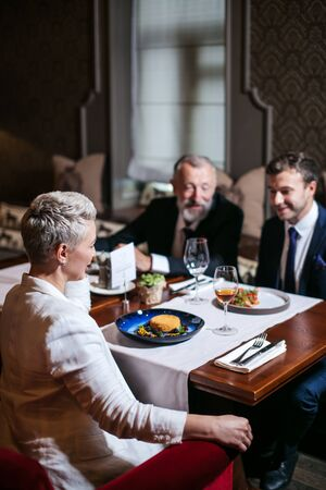 Group of generous friends enjoy dinner in beautiful restaurant, close up of blonde woman sitting with back to camera at table with delicious meal, right side shot