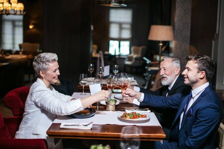 Happy business partners cheerfully raising hands with glasses of wine, gladly congratulate each other with successful deal, posing in luxury restaurant Banco de Imagens