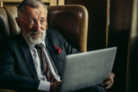 Portrait d'un vieux patron à tête blanche avec un visage ridé et une longue barbe épaisse posant directement devant la caméra exprime des émotions perplexes, plan horizontal
