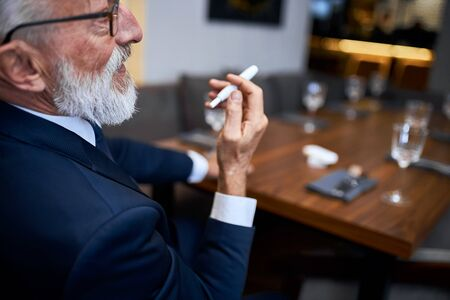 Elderly man vaping in closed public space. Smoking electronic cigarette in restaurant. Way to overcome nicotine addiction, old habit. Using cigarette on places smoking is not allowed 스톡 콘텐츠