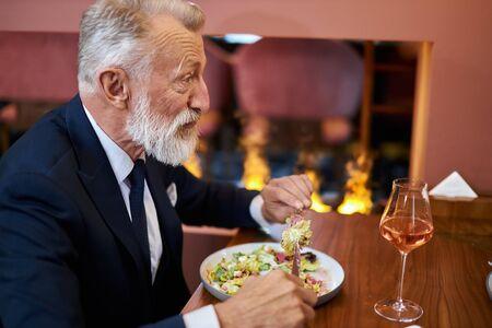 Elegant caucasian senior male sits in restaurant. Bearded man look and eat. Fireplace behind him. Horizontal image