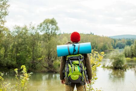 Young explorer standing on the bank of river in front of a fairy tale landscape, close up photo. lifestyle, free time
