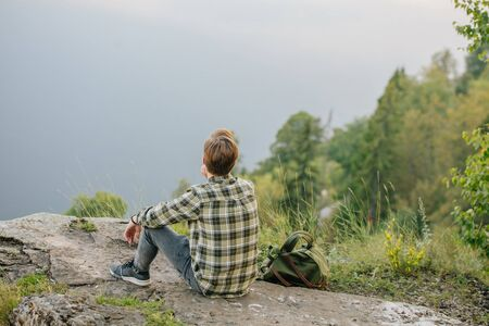 A lonely young man sits on the top of mountain, guy looking for inspiration, gets pleasure from fresh air and amazing nature, back view photo. blue sky and forest in the background of the photo