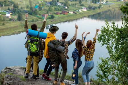 Young ambitious people with backpacks standing with raised hands on top of a mountain and enjoying valley view, happiness