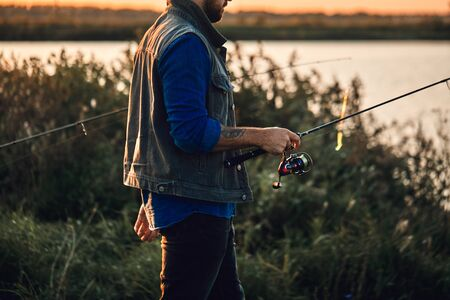 Caucasian adult bearded men stand near lake and fish. Sunset.