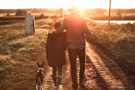 Father hugged son. They and dog walk along country road along lake to fishing spot. Sunset. Reklamní fotografie