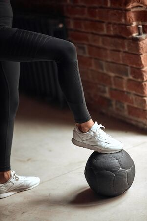 Young woman's leg in white sneakers on fitness bal at gym. Sport, healthy lifestyle concept