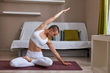 Beautiful caucasian woman in sportswear is doing yoga and raise hands left and right, crossed legs, hand on mat. Background light room