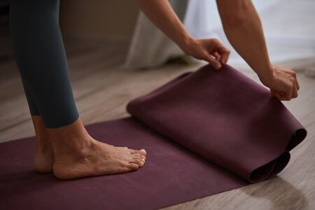 Young woman fold fitness or yoga mat on floor at home. Healthcare concept Stockfoto