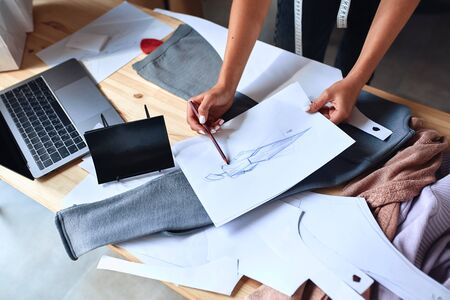 Top view on making sketch for new fashion collection. Laptop, papers, textile on table Фото со стока