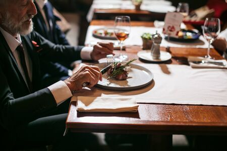 Solemn good natured man dinners with coworkers in pleasant place, cuts tasty specially prepared meat, looks at plate with no emotion, down shot Stock fotó