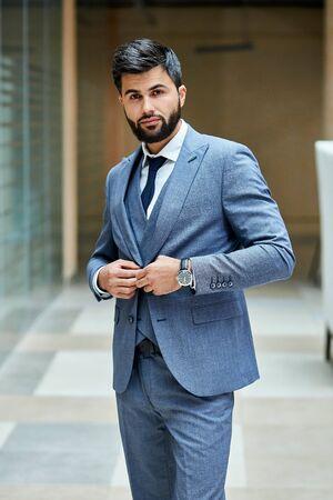 Elegant male in suit posing in street. Attractive brunette in grey suit, black haired Reklamní fotografie