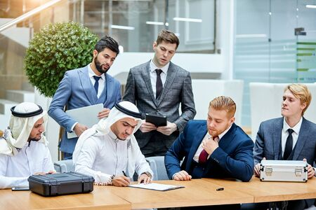Business meeting of sheikh and caucasian men, signing new contract. Buying new modern technology made by caucasians. Cases of money on table. Zdjęcie Seryjne - 132243111