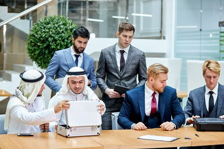 Sheikhs show money in case to buy new technology by caucasians. Business concept Zdjęcie Seryjne - 132245355