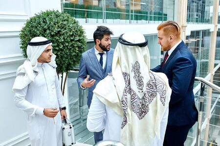 Caucasian men in tuxedo, sheikhs in white suit. Caucasians going to work with sheikhs, coopeation with sheikhs. Speak about new deal, finance