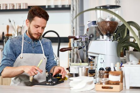 Calm serious male barista dressed in casual outfit and nice white apron, holds brush, looks down with calm face, working hard in coffee shop