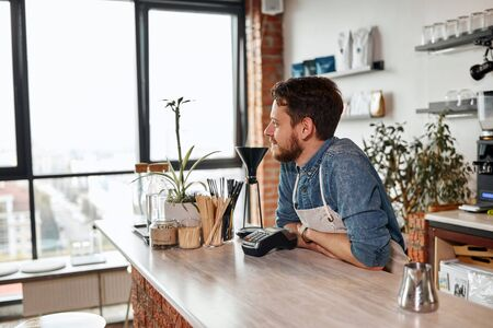 Young pleased man with thich beard looks away at big window, expresses calmness, waits for clients at brightly lighted room, relax, softness concept