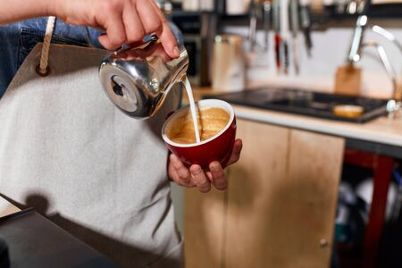 Hands of skillful young bartender pouring steamed milk from metal jug, making hot latte, holding red big cup, coffee making concept Stock fotó