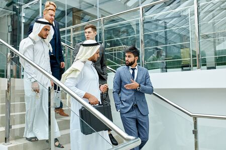 Sheikhs in white suits go down the stairs with caucasians Stock Photo