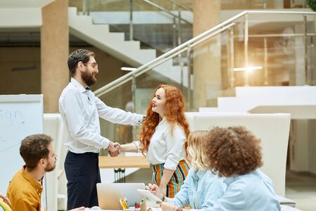 Decent, impressive middle aged manager friendly congratulates, young pretty female worker with successful job position, office work concept Imagens