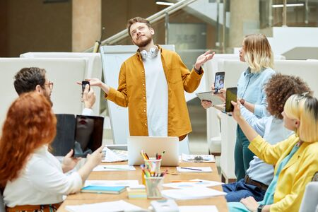 Successful handsome male coach stands in front of group of people, spreads hands sideways with relaxed expression, pleased by good work Stock Photo
