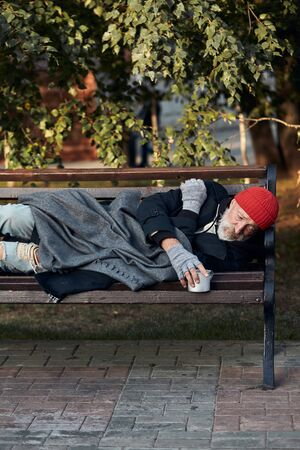 Vagrant male lying on street bench asking for money, for any help. Desperate and lonely homeless man without shelter Imagens