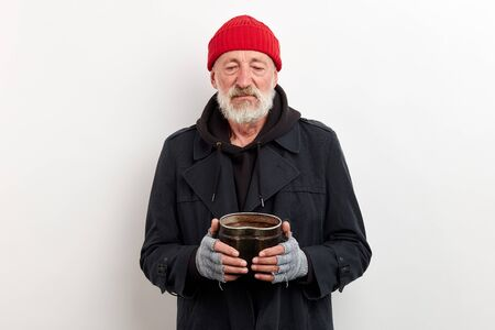 Mature bum in black coat and red cap on head holding iron can for raising money. Isolated over white background