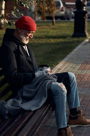 Hombre maduro sin refugio sentado en ropa de calle en un banco, sin comida ni dinero. El hombre inclinado bajó la cabeza hacia la taza para recolectar dinero. Vista lateral de la persona sin hogar en abrigo y gorra roja