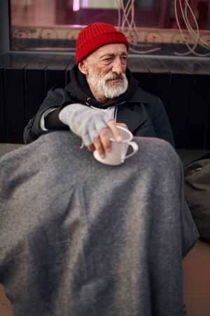 Homeless man begging in the center of city, sitting on the floor next to modern cafe and looking away. Homeless male wearing warm old clothes, red hat and wrap on legs.