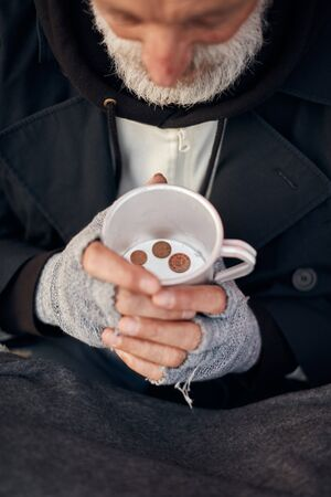 Hands of mature homeless male in grey gloves holding mug with coins. Poverty, hunger, helpless