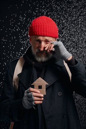 Senior street man wearing coat and red hat, holding house made by cardboard dream about own shelter and cry Zdjęcie Seryjne
