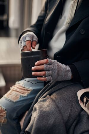 Homeless unrecognizable person holding money, dollar bill. Kind people help to poor. Beg for money concept