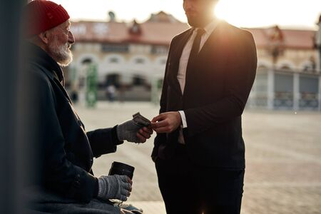 Homeless senior man hold out his hand to get money from unrecognizable rich man. Street life
