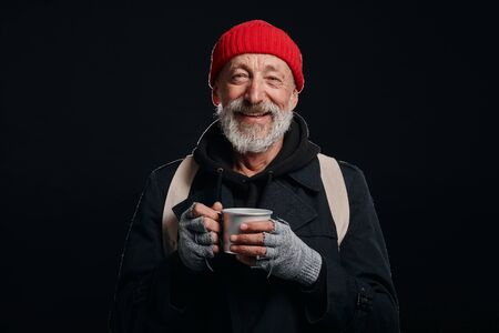 Bearded beggar male smiling, happy even living in street. Cheerful homeless man with mug of hot tea isolated over black background