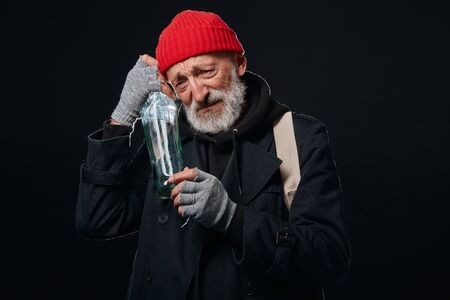 Old man with grey beard hugging empty bottle of alcohol. Male dressed in old street clothes isolated over black background