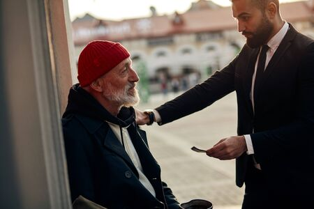 Poor senior man wearing coat, suffering from cold weather meet rich man in street, who helped him with money