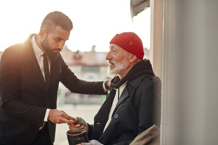 Businessman in tuxedo help to vagrant man sitting on street with rusty money jar. Rich man put one hand on shoulder of homeless person and give one dollar. Kind people, compassion, sympathy