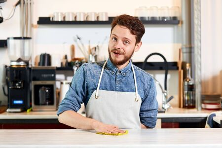 barista, wears jeans shirt and neat apron, stands at wooden counter, keeps one hand behind back, puts hand on table, cleans with duster, looks camera, opens mouth to say hi, professional concept
