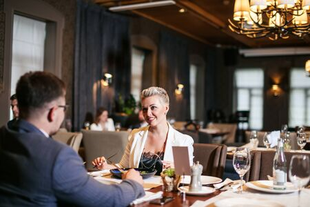 Close up of glorious optimistic young lady wears white unbuttoned jacket and black blouse, admiringly looks at business partner with eyes full of happiness at restaurant table