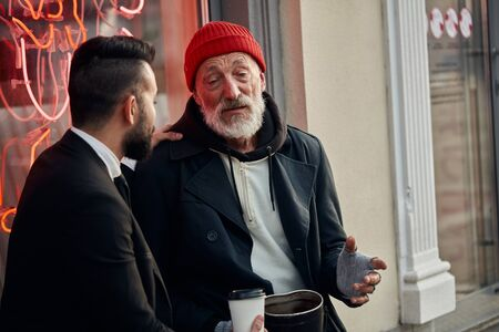 Compassionate man in black tuxedo sit listening to beggar males story about his life in street, talking Фото со стока