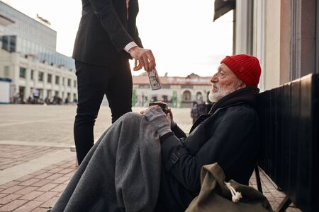 Rich man came up and help homeless man sitting on the floor. Help, money donation to vagrant male in the street