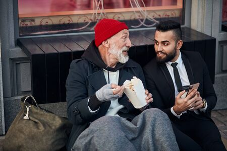 Rich man in black suit sit with phone, show interesting videos while beggar eating and talking. Senior tramp with grey beard wearing red hat and old warm clothes