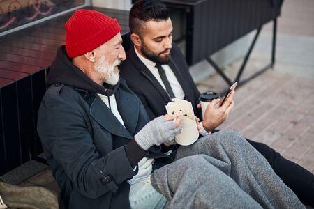 Handsome man in suit show smartphone to beggar man sitting on street
