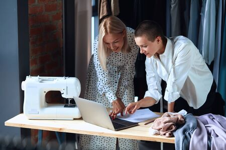 Beautiful European woman look at laptop while standing near table in workshop with clothes, laptop and sewing machine. Cheerful and happy to create together