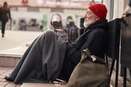 Beggar male sit with jar for money, wearing warm old clothes. Vagrant with grey beard, red hat and grey gloves freezing in the street