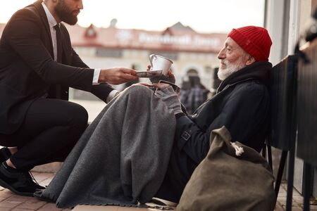 Kind man in suit hunkered down to homeless and give money donation, one dollar bill to beggar male Imagens
