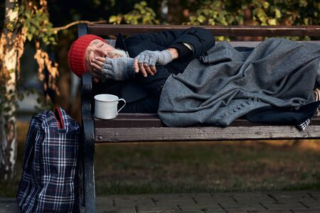 Homeless senior man lying on park bench, trembling from the cold. Cup for collecting money, coins next to him. 版權商用圖片