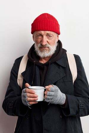 Homeless man wearing red hat and street clothes, look at camera with sadness. Beggar holding cup tea trying to warm up