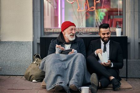 Smiling rich and poor men together sitting on street and eat while speaking. Happy despite social inequality Imagens